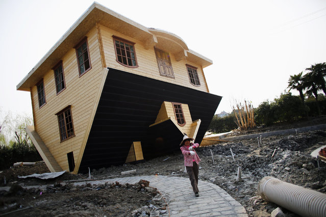 "A laborer works at an upside-down house under construction at Fengjing Ancient Town, Jinshan District, south of Shanghai, March 17, 2014. Workers are putting the final touches on this eccentric tourist attraction built at the ""China Folk Painting Village"". Furniture will also be placed upside down in the house, which is expected to open the public in April, according to local media. (Photo by Carlos Barria/Reuters)"
