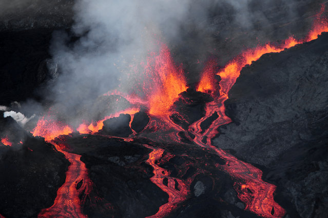 Lava flows out of the Piton de la Fournaise volcano as it erupts on May 17, 2015 on the French island of La Reunion in the Indian Ocean. The Piton de la Fournaise started to erupt early on May 17, with its last eruption dating back to February 4. (Photo by Richard Bouhet/AFP Photo)