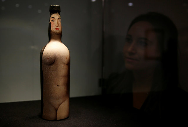 """A gallery assistant poses with painted bottle """"Femme-bouteille"""" by Rene Magritte during a media preview of the Impressionist and Modern Art sale at Christie's in London, Britain April 11, 2016. (Photo by Stefan Wermuth/Reuters)"""