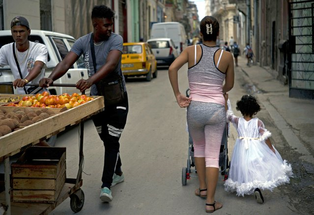 A girl in an angel costume walks with her family past vegetable vendors in Havana, Cuba, Wednesday, April 10, 2019. (Photo by Ramon Espinosa/AP Photo)