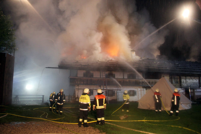 Firefighters try to extinguish a fire  in the Bavarian town of Schneizlreuth, Germany, early Saturday May 23, 2015. Police in Germany say six people are missing after a fire at a guesthouse in Bavaria. In a statement Saturday, police said the fire broke out overnight in a converted farmhouse in the town of Schneizlreuth, southeast of Munich near the border with Austria. (Photo by Ferdinand Farthofer/aktivnews/DPA via AP Photo)
