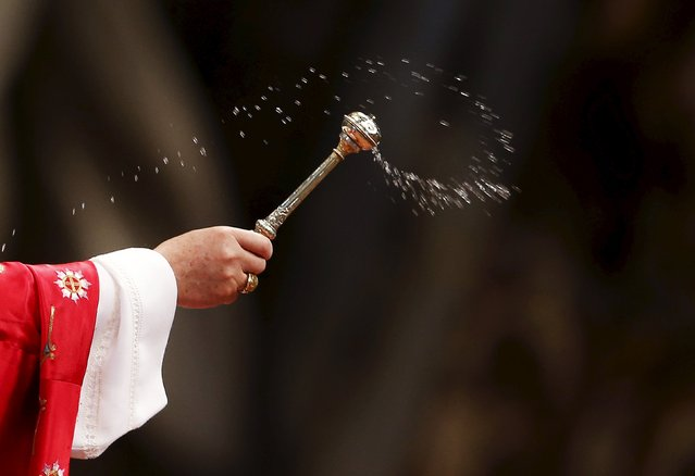 Pope Francis sprinkles holy water during a Mass of Pentecost at Saint Peter's Basilica at the Vatican May 24, 2015. (Photo by Alessandro Bianchi/Reuters)