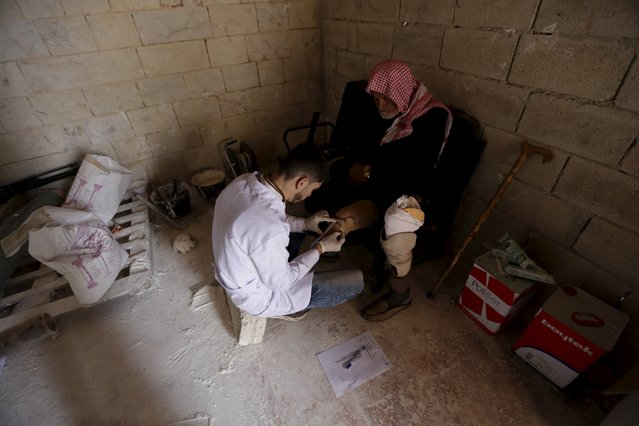 Khlouf, 25, prepares an artificial limb for a man with an amputated leg in the rebel-controlled area of Maaret al-Numan town in Idlib province, Syria March 20, 2016. (Photo by Khalil Ashawi/Reuters)