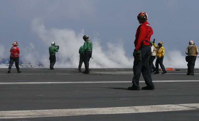 With smoke created by a F18 fighter jet taking off crewmen prepare the next one aboard the U.S. Navy aircraft carrier USS Carl Vinson (CVN 70) off the disputed South China Sea Friday, March 3, 2017. The U.S. military took journalists Friday to the carrier on routine patrol off the disputed South China Sea, sending a signal to China and American allies of its resolve to ensure freedom of navigation and overflight in one of the world's security hotspots. (Photo by Bullit Marquez/AP Photo)