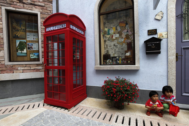Children pose for pictures at the replica of Austria's UNESCO heritage site, Hallstatt village, in China's southern city of Huizhou in Guangdong province June 1, 2012. Metals and mining company China Minmetals Corporation spent $940 million to build this controversial site and hopes to attract both tourists and property investors alike, according to local newspaper reports. (Photo by Tyrone Siu/Reuters)
