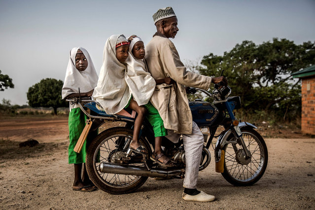 A group of Fulani girls gather prior to arriving to the school grounds along his father while riding a motorbike before the beginning of the day's lessons at Wuro Fulbe Nomadic School in Kacha Grazing Reserve for Fulani people, Kaduna State, Nigeria, on April 19, 2019. (Photo by Luis Tato/AFP Photo)