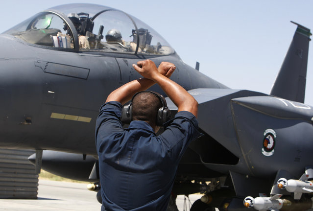 A member of the ground crew signals to the pilot of a U.S. Air Force F-15E fighter jet before take off at Bagram air base, north of Kabul, August 10, 2009. (Photo by Oleg Popov/Reuters)