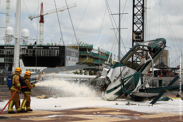 Firefighters spray foam at the scene where a helicopter crashed while installing a large Christmas Tree at the Viaduct Harbour on November 23, 2011 in Auckland, New Zealand