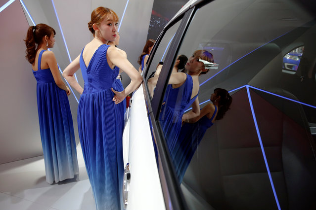 Performers are reflected in a displayed vehicle before going onto the stage during the Auto China 2016 auto show in Beijing, China, April 29, 2016. (Photo by Damir Sagolj/Reuters)