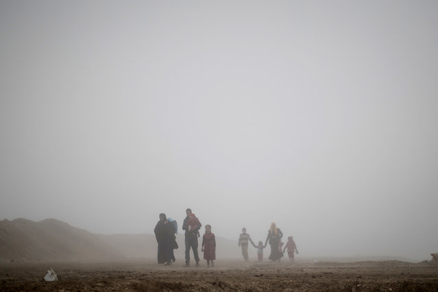 In this Friday, March 17, 2017 file photo, displaced people walk through heavy fog during fighting between Iraqi security forces and Islamic State militants in west Mosul, Iraq.. (Photo by Felipe Dana/AP Photo)