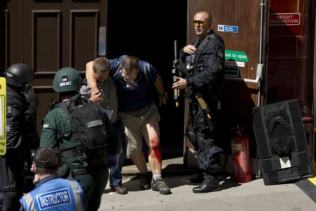 During a training exercise for London's emergency services, a casualty is helped to leave the disused Aldwych underground train station in London, Tuesday, June 30, 2015. Hundreds of British police are taking part in a major counter-terror exercise in London, testing the abilities of emergency services to respond to a Tunisia-style attack of extremists with firearms. The exercise dubbed Operation Strong Tower has been planned for six months and is not connected to the recent attack at a north African beach resort. (Photo by Matt Dunham/AP Photo)