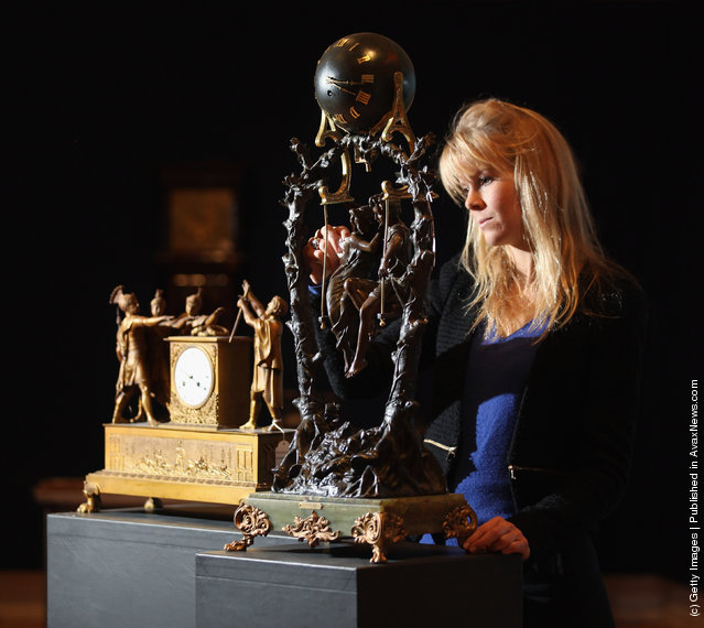 A gallery assistant cleans an ormolu mantel clock next to spelter and onyx mystery swinging clock in Bonhams auction house