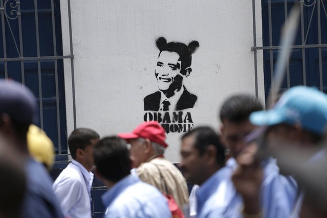 Union members of Empresas Polar's beer factory pass in front of a graffiti depicting U.S. President Barack Obama as they take part in a demonstration in Caracas, July 2, 2015. Union members said on Thursday they had shut two breweries belonging to the country's largest beer company over a wage dispute, setting the stage for a potential shortage in the alcohol-loving nation. (Photo by Jorge Dan Lopez/Reuters)