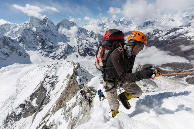 Danuru Sherpa, a veteran guide, pulls his way up a fixed line between Camp 1 and Camp 2 on Ama Dablam. To help climbers reach the top of the beautiful, steep peak, Sherpas attach ropes to the snow and ice for clients hold on to during ascent. (Photo by Aaron Huey/National Geographic)