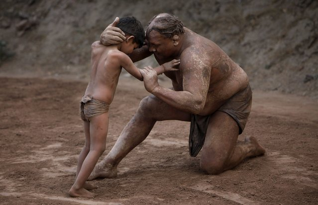 A Kushti wrestler gives tips to a young wrester during a training session, in Lahore, Pakistan, Saturday, May 7, 2016. Kushti, an Indo-Pakistani form of wrestling, is several thousand years old and is a national sport in Pakistan. (Photo by K.M. Chaudary/AP Photo)
