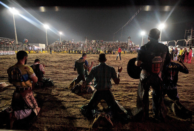 Riders pray before competing at a rodeo event in Monte Negro, south of the Amazon basin, Rondonia state, Brazil on August 30, 2019. (Photo by Carl De Souza/AFP Photo)