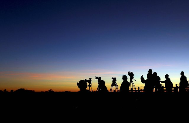 Tourists sets up cameras to photograph the sunrise in Uluru, Australia, Tuesday, April 22, 2014. The Duke and Duchess of Cambridge will visit Uluru Tuesday during their three-week tour of Australia and New Zealand, the first official trip overseas with their son, Prince George. (Photo by Rob Griffith/AP Photo)