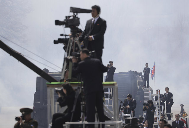 North Korean media stand on ladders as they photograph and film a military parade on Saturday, April 15, 2017, in Pyongyang, North Korea to celebrate the 105th birth anniversary of Kim Il Sung, the country's late founder and grandfather of current ruler Kim Jong Un. (Photo by Wong Maye-E/AP Photo)