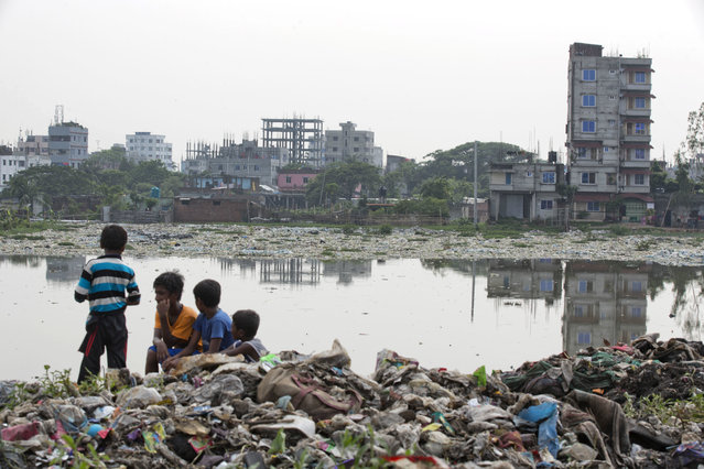In this June 4, 2018, file photo, Bangladeshi children sit on garbage piled up by the river Buriganga in Hazaribagh area in Dhaka, Bangladesh. A new report by the United Nations children's agency says the lives and futures of more than 19 million Bangladeshi children are at risk from colossal impacts of devastating floods, cyclones and other environmental disasters linked to climate change. The UNICEF report released Friday, April 5, 2019 said the tally includes Rohingya refugee children from Myanmar who are living in squalid camps in southern Bangladesh. (Photo by A.M. Ahad/AP Photo/File)