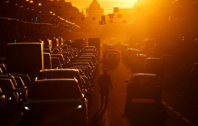 A pedestrian walks amidst traffic lanes along Nevsky Avenue, the city's main thoroughfare, during sunset in Saint Petersburg, Russia on April 12, 2019. (Photo by Anton Vaganov/Reuters)