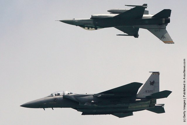 An  F-15SG  (bottom) and the F-16C  fighters from the Republic of Singapore Air Force perform during the opening day of the Singapore Airshow 2012 at the Changi Exhibition Cenre
