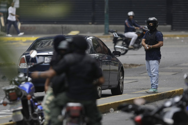 An armed member of a pro-government militia, right, stands on a median strip after hassling anti-government protesters attempting to march to the Supreme Court in downtown Caracas, Venezuela, Wednesday, May 10, 2017. (Photo by Fernando Llano/AP Photo)