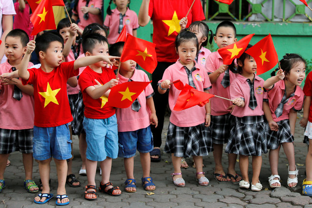 Children look at the motorcade transporting U.S. President Barack Obama before an arrival ceremony at the presidential palace in Hanoi, Vietnam May 23, 2016. (Photo by Carlos Barria/Reuters)
