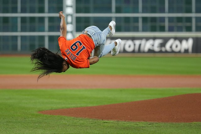 Olympic gymnastics gold medalist and Houston native Simone Biles performs a flip before throwing out a ceremonial first pitch prior to game two of the World Series between the Houston Astros and the Washington Nationals at Minute Maid Park in Houston on October 23, 2019. (Photo by Troy Taormina/USA TODAY Sports)