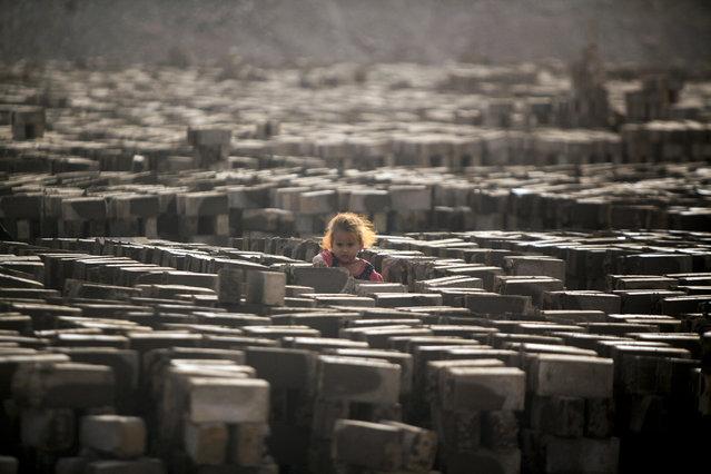An Iraqi girl stands amid bricks baking dry in the sun at a brick factory near the central Iraqi shrine city of Najaf on May 16, 2017. (Photo by Haidar Hamdani/AFP Photo)