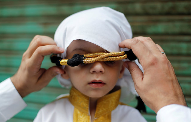 A Muslim man adjusts the head gear of his son during a religious procession to mark Eid-e-Milad-ul-Nabi, or birthday celebrations of Prophet Mohammad, in the old quarters of Delhi, India, November 10, 2019. (Photo by Adnan Abidi/Reuters)