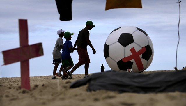 """People walk past an installation of giant soccer balls with red crosses on them and a fake grave in a """"slum area"""" which was set up as a form of protest on the Copacabana beach in Rio de Janeiro, June 10, 2014. (Photo by Wong Maye-E/Associated Press)"""