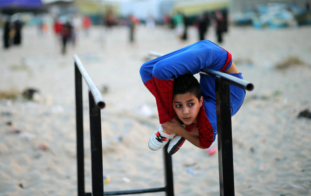 "Palestinian boy Mohamad al-Sheikh, 12, who is nicknamed ""Spiderman"" and hopes to break the Guinness world records with his bizarre feats of contortion, demonstrates acrobatics skills on a beach in Gaza City June 2, 2016. (Photo by Mohammed Salem/Reuters)"