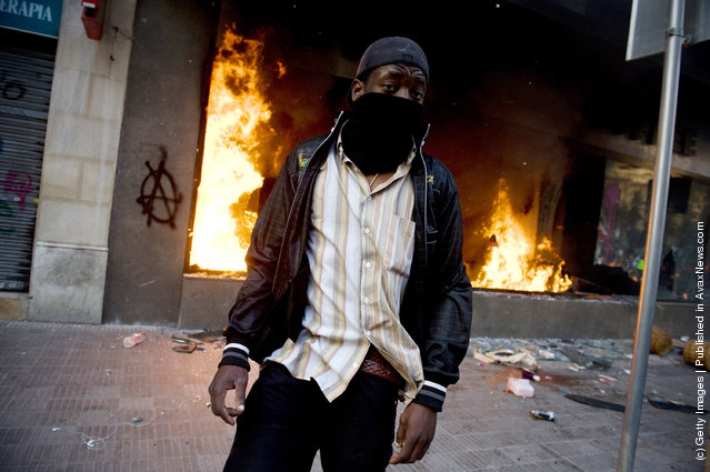A masked demonstrator walks past a burning Starbucks during heavy clashes with riot police during a 24-hour strike on March 29, 2012 in Barcelona, Spain