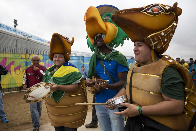 Brazil soccer fans in costume play instruments outside Arena Corinthians stadium in Sao Paulo, Brazil, Wednesday, June 11, 2014. The World Cup soccer tournament starts Thursday. (Photo by Rodrigo Abd/AP Photo)