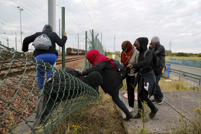 Migrants make their way across a fence near near train tracks as they attempt to access the Channel Tunnel in Frethun, near Calais, France, July 29, 2015. (Photo by Pascal Rossignol/Reuters)