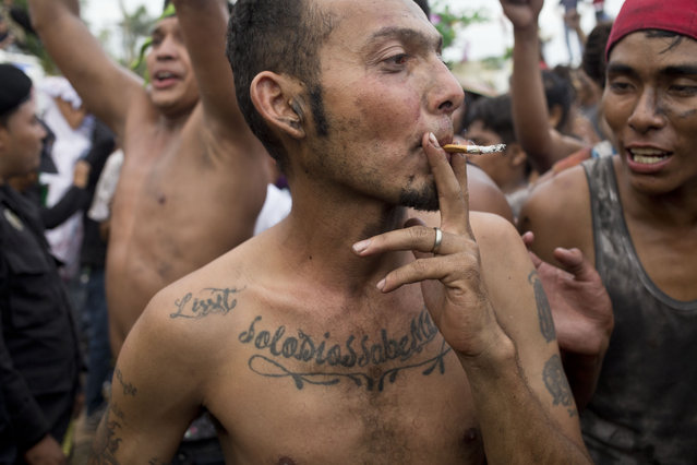 A man smokes a cigarette during the festivities in honor of Santo Domingo de Guzman in Managua, Nicaragua, Saturday, August 1, 2015. Some of the faithful coat their bodies black oil, red paint and wear traditional clothes annually, as a promise for a prayer or miracle they believe was performed or answered by Managua's patron saint, Santo Domingo de Guzman. (Photo by Esteban Felix/AP Photo)