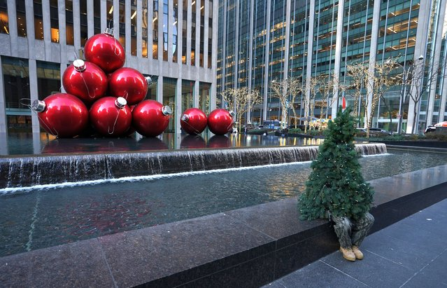 "Sreet performer Thomas Liberto from Bel Air, Maryland, who goes by the social media name ""Mr. Christmas Tree"" sits by Christmas decorations around midtown New York on December 19, 2019. Mr. Christmas Tree aka Liberto, who begins the holiday season traveling from Maryland to NYC, has been walking around in festive costume for the last five years. (Photo by Timothy A. Clary/AFP Photo)"
