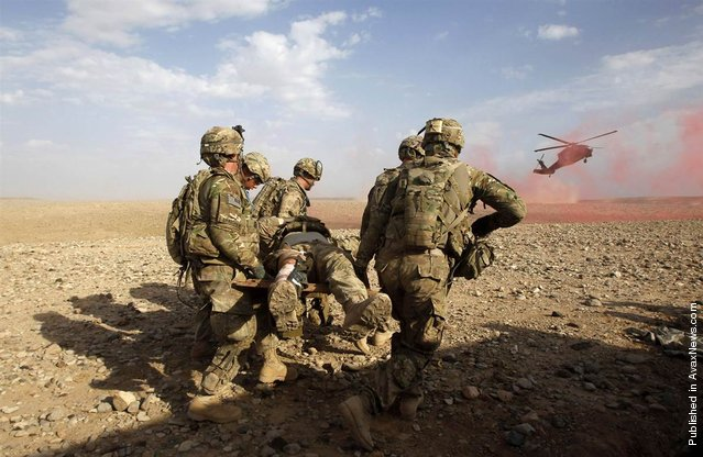 U.S. Army soldiers carry an injured comrade to a helicopter during a firefight with Taliban in the Maiwand district of Kandahar province, southern Afghanistan, April 9, 2012