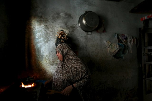 A Palestinian woman makes tea inside her house during power cut at Shatti (beach) refugee camp in Gaza City July 23, 2015. (Photo by Mohammed Salem/Reuters)