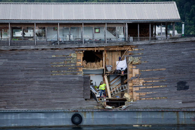 A crew member inspects damages on the hull of a full-size replica of the Ark of Noah after it crashed into a moored coast guard vessel in Oslo harbour on June 10, 2016. (Photo by Hakon Mosvold Larsen/AFP Photo/NTB Scanpix)