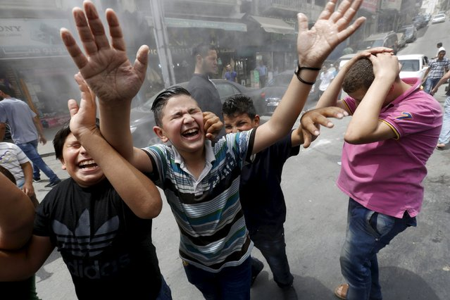 Children react as personnel from the Greater Amman Municipality spray them with a water sprinkler in order to cool them down, as part of measures to ease the effect of a heatwave, in Amman, Jordan August 3, 2015. (Photo by Muhammad Hamed/Reuters)