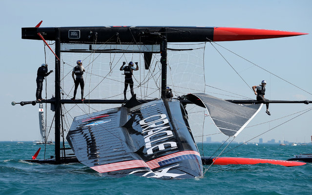 Sailing -Americas Cup World Series, Chicago, Illinois on June 10, 2016. The crew of Oracle Team USA stand on their capsized boat during a practice session for the America's Cup World Series sailing event. (Photo by Jim Young/Reuters)
