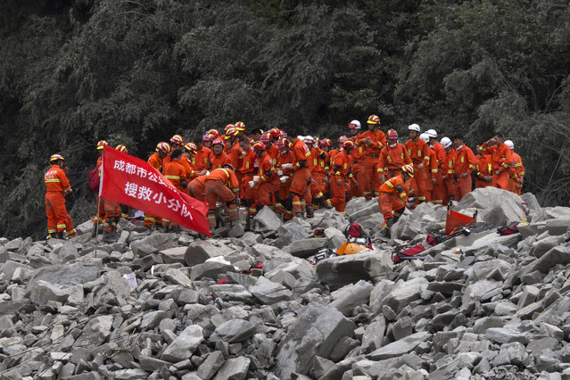Rescue workers gather for a canteen break at the site of a landslide in Xinmo village in Maoxian County in southwestern China's Sichuan Province, Sunday, June 25, 2017. (Photo by Ng Han Guan/AP Photo)