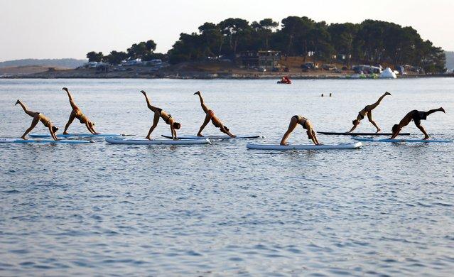 People practise Metta Float Yoga at the adriatic cost in Medulin, Croatia August 6, 2015. (Photo by Pawel Kopczynski/Reuters)