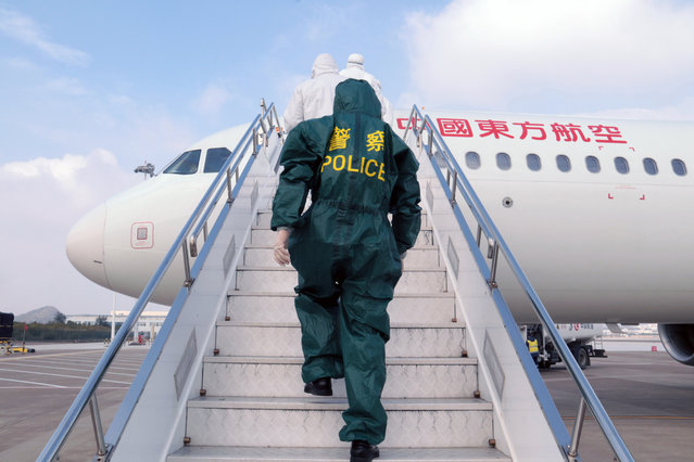 Police and medical personnel enter a plane to take temperature tests of passengers on board at the airport in Zhoushan City, Zhejiang Province, China, 28 January 2020. The outbreak of coronavirus in China has so far claimed at least 100 lives and infected more than 4,500 others, according to media reports. Governments around the world are taking preventative measures to health the spread of the virus. (Photo by EPA/EFE/China Stringer Network)