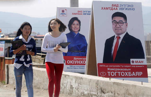 Women walk past posters of candidates from Mongolian People's Party (MAH) on the outskirts of Ulan Bator, Mongolia, June 27, 2016. (Photo by Jason Lee/Reuters)