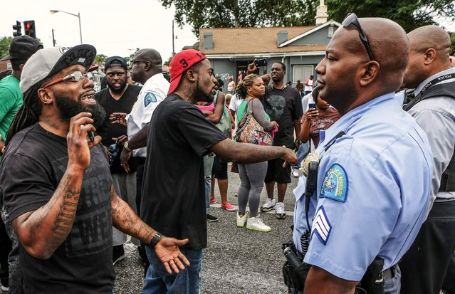 Area residents talk to police after a shooting incident in St. Louis, Missouri August 19, 2015. Police fatally shot a black man they say pointed a gun at them, drawing angry crowds and recalling the racial tensions sparked by the killing of an unarmed African-American teen in nearby Ferguson, Missouri, just over a year ago. (Photo by Lawrence Bryant/Reuters)