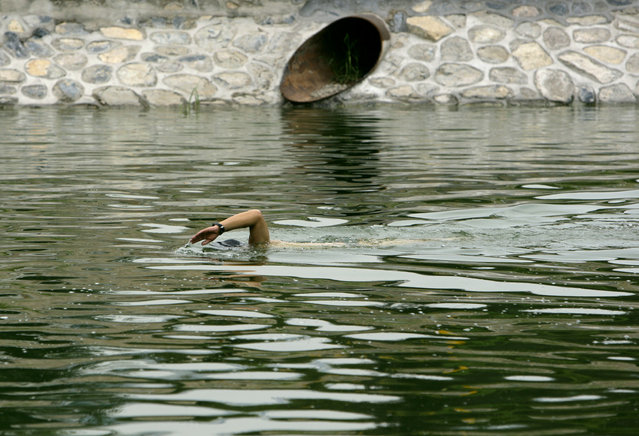 A man swims in a polluted canal in the centre of Beijing August 16, 2007. China's capital, host of the 2008 Summer Olympics, warned on Thursday that heat had put some of its lakes at risk of algae blooms, similar to those that have cut water supplies elsewhere in the country. (Photo by David Gray/Reuters)
