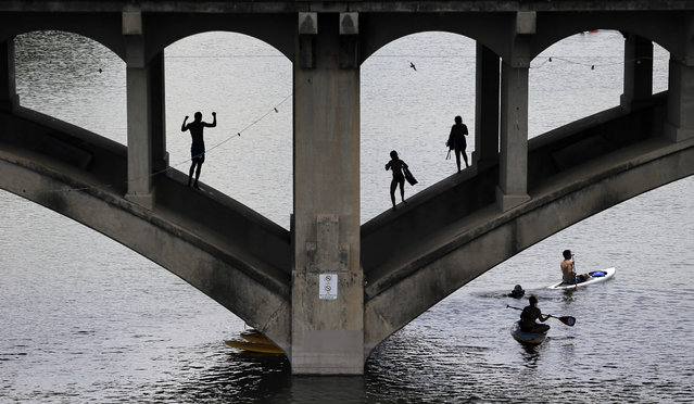 Kayakers and swimmers play on Lady Bird Lake near a bridge, Thursday, June 30, 2016, in Austin, Texas. Lady Bird Lake had been closed to water recreation earlier in the month after heavy flooding and swift currents, but businesses and activities have returned to normal. (Photo by Eric Gay/AP Photo)