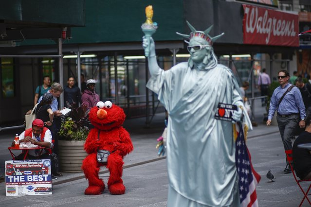 Jorge, an immigrant from Mexico, and dressed as the Sesame Street character Elmo rests in Times Square, New York July 30, 2014. (Photo by Eduardo Munoz/Reuters)